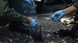 Petugas kepolisian Thailand menggunakan peralatan magnetik saat menyisir puing-puing di depan kuil Erawan, Bangkok, Thailand, (18/8/2015). Ledakan bom tersebut menewaskan 22 orang. (AFP PHOTO/Christophe ARCHAMBAULT )