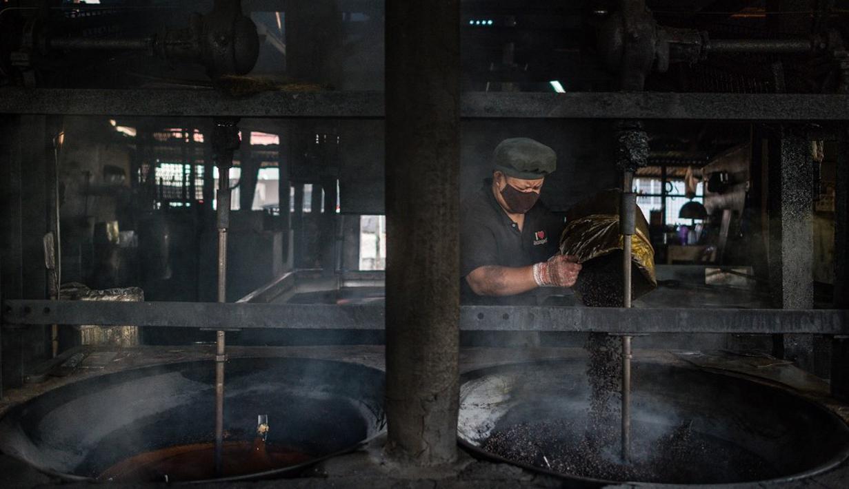 Pekerja memanggang biji kopi di Pabrik Kopi Antong, Taiping, Perak, Malaysia, 29 September 2020. Pabrik Kopi Antong menggunakan mesin antik dan metode pemanggangan tradisional untuk menghasilkan bubuk sarat kafein yang terkenal selama 87 tahun. (Mohd RASFAN/AFP)