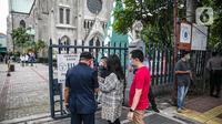 Para Jemaat memperlihatkan bukti pendaftaran untuk mengikuti ibadah di Gereja Katedral, Jakarta, Kamis (24/12/2020). Kapasitas gereja untuk ibadat misa Natal sebanyak 309 kursi, yaitu 20 persen dari kapasitas Gereja Katedral. (Liputan6.com/Faizal Fanani)
