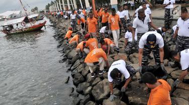 Prajurit Pusat Hidrografi dan Oseanografi TNI AL bersama petugas keamanan Ancol membersihkan sampah di sepanjang Pantai Ancol, Jakarta, Selasa (22/1). Kegiatan itu dilakukan mulai dari Pantai Lagoon hingga dermaga Marina. (Merdeka.com/Iqbal S. Nugroho)