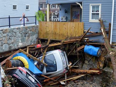 Warga berkumpul untuk melihat sejumlah mobil yang tersangkut di sebuah jembatan di Ellicott City, Maryland, Amerika Serikat, Senin (28/5). Banjir bandang Maryland diakibatkan meluapnya Sungai Patapsco. (AP Photo/David McFadden)