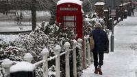 Seorang pria berjalan melewati box telefon yang tertutup salju tebal di Marlow, Inggris, Senin (11/12/2017). (AP)