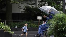 Seorang pria memakai masker melihat ponselnya di sebuah taman di Tokyo, Rabu, (23/9/2020). Badai tropis di Samudra Pasifik perlahan mendekati wilayah Tokyo pada hari Rabu, dan para pejabat mendesak penduduk berhati-hati dari perkiraan hujan lebat dan hembusan angin. (AP Photo/Eugene Hoshiko)