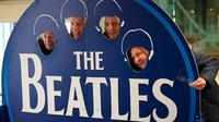 Wisatawan berpose disebuah papan Beatles di kafe kopi bertema The Beatles di Liverpool, , Inggris, (2/3). Warga Liverpool Peringati 50 tahun terakhir kali The Beatles melakukan konser di kota asal mereka ini. (REUTERS/Phil Noble)