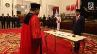 Arief Hidayat menandatangani berita acara pengambilan sumpah jabatan Hakim Konstitusi periode 2018-2023 di Istana Negara, Jakarta, Selasa (27/3). (Liputan6.com/Angga Yuniar)