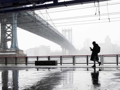 Seorang pejalan kaki melintas di dekat jembatan Manhattan saat badai salju di bawah drive Franklin Delano Roosevelt di New York (21/3). Badai salju yang melanda sebagian Amerika Serikat telah membawa salju dan angin kencang. (AP Photo / Mary Altaffer)
