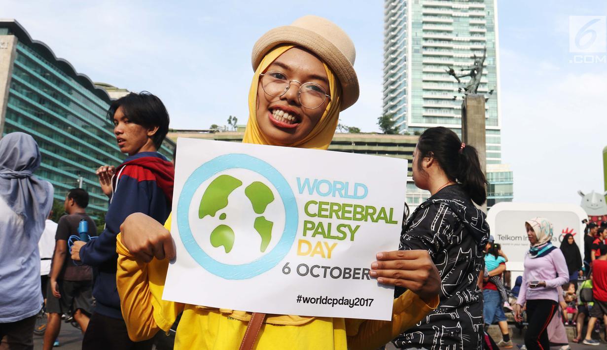 Relawan disabilitas membawa poster Peringatan Hari Cerebral Palsy Sedunia di area Car Free Day, Bundaran HI, Jakarta, Minggu (8/10). Kegiatan itu memperingati Hari Cerebral Palsy Sedunia yang jatuh pada tanggal 6 Oktober. (Liputan6.com/Angga Yuniar)