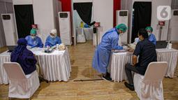 Petugas medis mendata dan memeriksa kondisi karyawan di lingkungan KPU RI saat vaksinasi COVID-19 di Gedung KPU, Jakarta, Rabu (17/3/2021). Sebanyak 549 karyawan di lingkungan KPU RI mengikuti vaksinasi COVID-19. (Liputan6.com/Faizal Fanani)