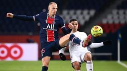 Bek Paris Saint-Germain, Mitchel Bakker (kiri), berebut bola dengan striker Bordeaux, Hatem Ben Arfa, dalam laga lanjutan Liga Prancis 2020/21 di Parc de Princes Stadium, Sabtu (28/11/2020) waktu setempat. Hasil akhir PSG dan Bordeaux bermain imbang 2-2. (AFP/Franck Fife).