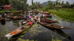 Para pria Kashmir menjual produk mereka di pasar sayur terapung di Danau Dal di Srinagar, Kashmir yang dikuasai India pada 26 Juli 2020. Sayuran yang diperdagangkan di pasar terapung ini disuplai ke Srinagar dan banyak kota di lembah Kashmir. (AP Photo/Dar Yasin)