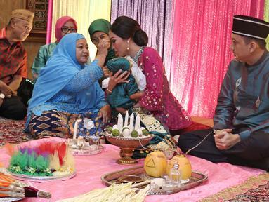 Ayu Dewi bersama suami Regi Datau saat prosesi Mohuntingo di kawasan Tebet, Jakarta, Minggu (27/08). Ayu Dewi dan Regi Datau menggelar acara Mohuntingo atau potong rambut anak keduanya bernama Mohamad Aqlan Ukasyah Datau. (Liputan6.com/Herman Zakharia)