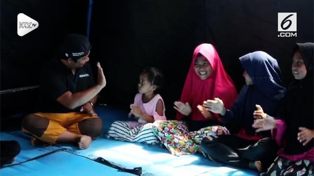 Petugas Kementrian Sosial melakukan trauma healing bagi anak-anak korban gempa Palu. Para anak diajak untuk bermain dan bernyanyi dengan ceria.