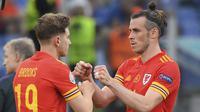 Striker Wales, Gareth Bale (kanan) digantikan oleh gelandang David Brooks saat melawan Italia dalam laga Grup A Euro 2020 di Olimpico Stadium, Roma, Minggu (20/6/2021) malam WIB. (Foto: AP/Pool/Alberto Lingria)