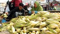 Seorang pedagang jagung melayani pembeli di Jalan Raya Bogor, Bogor, Kamis (31/12/2015). Jelang malam pergantian tahun 2016, sejumlah pedagang jagung musiman menggelar dagangannya di sepanjang Jalan Raya Bogor. (Liputan6.com/Helmi Fithriansyah)