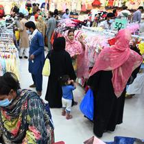 Orang-orang memadati toko saat berbelanja menjelang perayaan Idul Fitri yang akan datang di tengah pandemi corona Covid-19, di Rawalpindi, Pakistan pada 5 Mei 2021. Pusat perbelanjaan ramai oleh warga Pakistan yang berbelanja aneka kebutuhan untuk menyambut Lebaran. (Farooq NAEEM / AFP)