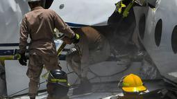 Petugas pemadam kebakaran berada di lokasi pesawat jet pribadi Gulfstream G200 yang tergelincir dari landasan saat mendarat di Bandara Tegucigalpa, Honduras, Selasa (22/5). Pesawat itu terbang dari Austin, Texas pada Selasa pagi. (AFP/Orlando SIERRA)