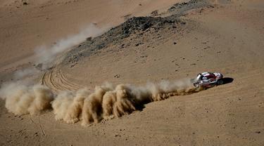 Pembalap Toyota Gazoo Racing Frenando Alonso dan Marc Coma bersaing pada stage pertama Reli Dakar 2020 antara Jeddah dan Al Wajh, Arab Saudi, Minggu (5/1/2020). Alonso mencetak sejarah sebagai juara dunia Formula 1 (F1) pertama yang berlaga di ajang Reli Dakar. (FRANCK FIFE/AFP)