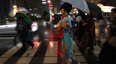 "Seorang wanita Jepang tersenyum mengenakan pakaian tradisional saat berjalan di jalan setelah menghadiri peragaan busana kimono di Oita (18/10/2019). Pada zaman sekarang, kimono berbentuk seperti huruf ""T"", mirip mantel berlengan panjang dan berkerah. (AP Photo/Christophe Ena)"