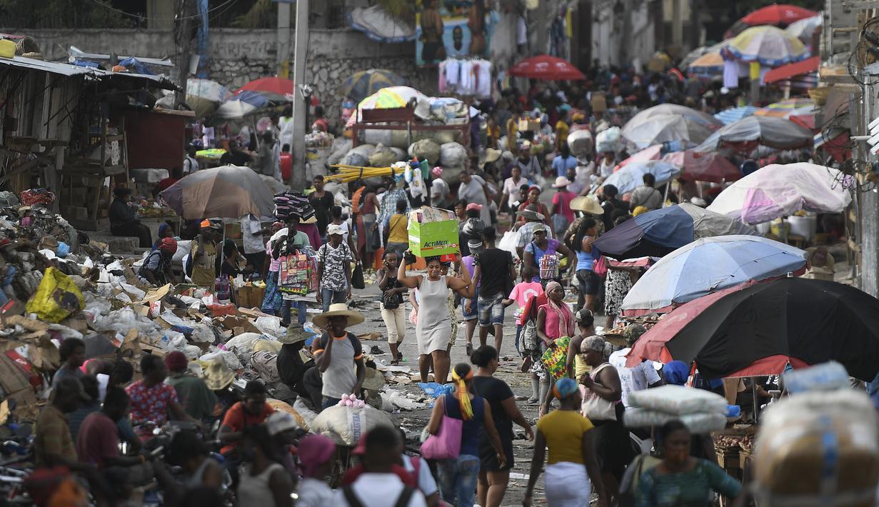Seorang perempuan membawa baskom dengan barang-barangnya di pasar Petion-Ville di Port-au-Prince, empat hari setelah pembunuhan Presiden Haiti Jovenel Moise, Minggu (11/7/2021). Moïse tewas dibunuh dalam serangan di kediaman pribadinya, pada Rabu 7 Juli 2021 dini hari. (AP Photo/Matias Delacroix)