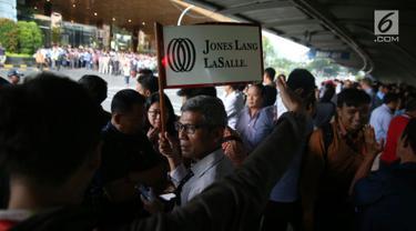 Sejumlah karyawan berkumpul di halte Bursa Efek Indonesia (BEI) saat balkon lantai 1 bangunan ambruk, Jakarta, Senin (15/1). (Liputan6.com/Johan Tallo)