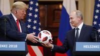 Presiden Rusia Vladimir Putin memberikan bola Piala Dunia 2018 kepada Presiden Amerika Serikat, Donald Trump selama konferensi pers bersama usai pertemuan mereka di Istana Presiden di Helsinki, Finlandia, Senin (16/7). (AP/Alexander Zemlianichenko)