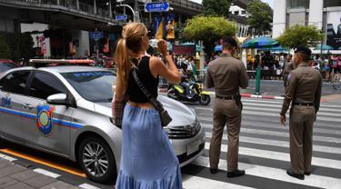 Seorang wanita menunggu untuk menyeberang jalan ke Kuil Erawan di Bangkok  (2/8/2019). Sedikitnya ada lima lokasi atau titik ledakan. Seperti di bawah halte BTS (Bangkok Sky Train) Chong Nonsi, persimpangan 57/1 Jalan Rama IX. (AFP Photo/Mladen Antonov)