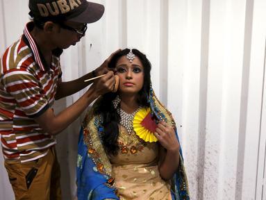Seorang model sedang di rias dibelakang panggung saat mengikuti lomba rias pengantin lokal di Karachi, Pakistan, 22 Maret 2016.Sejumlah wanita mengikuti lomba yang diadakan di sebuah pusat pembelajaan. (REUTERS / Akhtar Soomro)