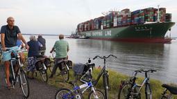 Pengendara sepeda melihat kapal kontainer CSCL Jupiter Hong Kong yang terdampar di muara Westerschelde di dekat kota Bath di Belanda setelah insiden grounding (14/8).  (AFP PHOTO/Belga/Kristof Van Accom/Belgium Out)