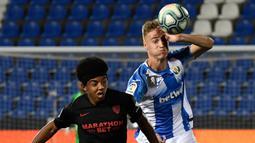 Bek Sevilla, Jules Kounde, berebut bola dengan striker Leganes, Manu Garrido, pada laga lanjutan La Liga pekan ke-33 di Estadio Municipal de Butarque, Rabu (1/7/2020) dini hari WIB. Sevilla menang 3-0 atas Leganes. (AFP/Pierre-Philippe Marcou)