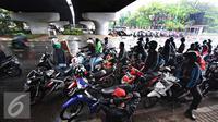 Pengendara sepeda motor berteduh di bawah flyover saat hujan turun, Jakarta, Senin (16/11). Petugas kepolisian akan menerapkan tilang dengan denda maksimal Rp250.000. (Liputan6.com/Immanuel Antonius)