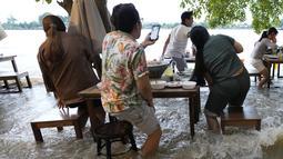 Pelanggan Chaopraya Antique Café di tepi sungai menikmati ketinggian air di Sungai Chao Phraya dekat Bangkok, Thailand, Kamis (7/10/2021). Karena kebanjiran, alih-alih kursi kosong dan meja kosong justru restoran penuh seperti biasanya bagi para pencinta santapan 'hot-pot'. (AP Photo/Sakchai Lalit)