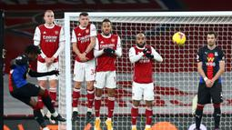 Gelandang Crystal Palace, Eberechi Eze (kiri) melepaskan tendangan bebas ke gawang Arsenal dalam laga lanjutan Liga Inggris 2020/21 di Emirates Stadium, Kamis (14/1/2021). Crystal Palace bermain imbang 0-0 dengan Arsenal. (AFP/Julian Finney/Pool)