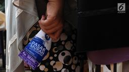 Seorang warga membawa brosur di Kantor AHY Foundation, Jakarta, Rabu (13/6). Harga paket sembako tersebut dijual kepada warga Kelurahan Petogokan berisi 5 kg Berat, 1 Liter minyak goreng dan 1 kg daging sapi. (Liputan6.com/JohanTallo)