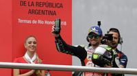 Pembalap LCR Honda, Cal Crutchlow merayakan kemenangannya pada balapan MotoGP Argentina di atas podium Sirkuit Termas de Rio Hondo, Minggu (8/4). Kemenangan ini menempatkan Crutchlow di puncak klasemen sementara dengan poin 38. (AP/Natacha Pisarenko)
