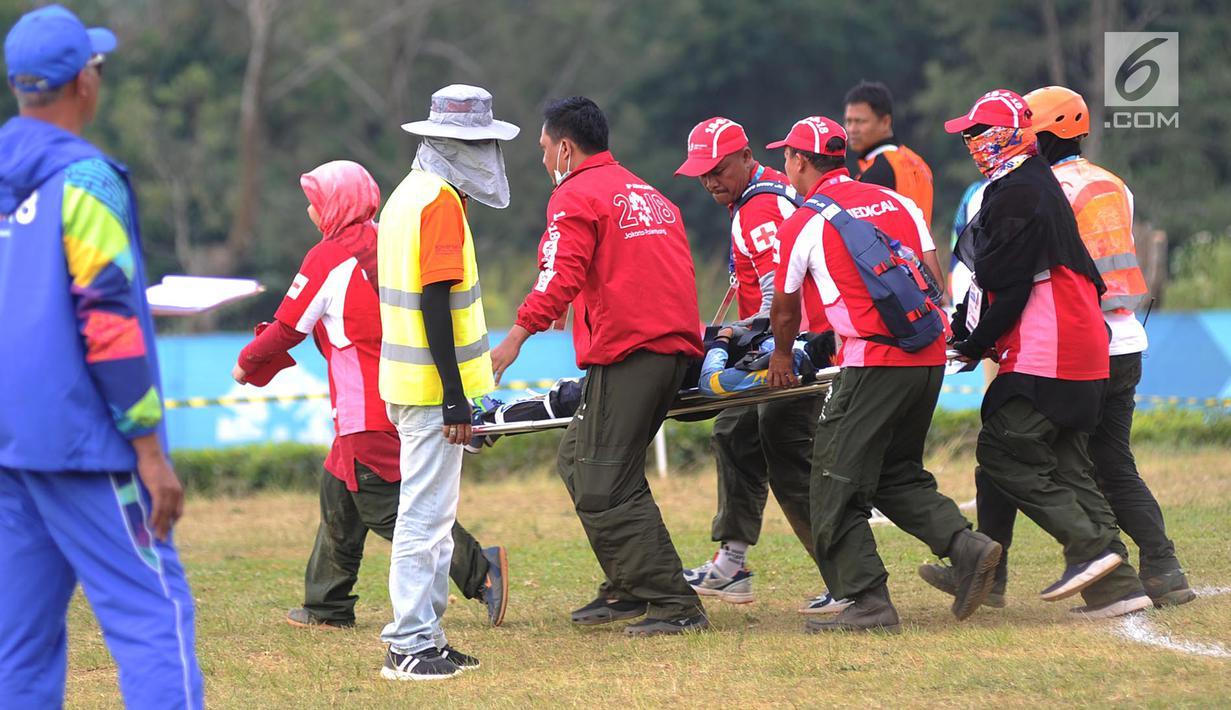 Petugas mengevakuasi atlet paralayang putri asal Malaysia Sharifah Nadiah Wafa saat bertanding pada nomor ketepatan mendarat Asian Games 2018, Bogor (21/8). Sharifah diduga mengalami cedera bagian pinggul kaki kanan ke bawah. (Merdeka.com/Arie Basuki)