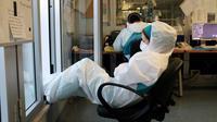 Seorang perawat beristirahat di pagi hari setelah shift malam selama 12 jam di rumah sakit Cremona, tenggara Milan, Lombardy, 12 Maret 2020. Para pekerja kesehatan Italia kelelahan setelah selama bermingu-minggu mereka yang berada di garda terdepan memerangi pandemi virus corona. (Paolo MIRANDA/AFP)