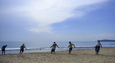 Para nelayan Sri Lanka menarik jaring ikan di pantai di Trincomalee (5/5). Trincomalee adalah kota pelabuhan di bagian timur Sri Lanka. (AFP Photo/Ishara S Kodikara)