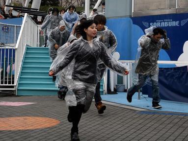 Sejumlah peserta memakai mantel plastik saat mengikuti simulasi evakuasi anti-rudal di taman hiburan Tokyo Dome City, Jepang, (22/1). Di tengah balistik Korea Utara, warga Jepang menggelar simulasi evakuasi anti-rudal. (AFP Photo/Toshifumi Kitamura)