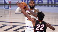 Pebasket Los Angeles Lakers, LeBron James, berusaha melewati pebasket Miami Heat, Jimmy Butler, pada laga Gim ketiga Final NBA, Senin (5/10/2020). Miami Heat menang dengan skor 115-104. (AP Photo/Mark J. Terrill)