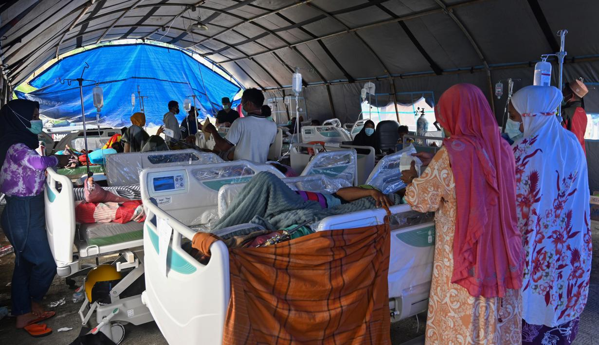 Orang-orang yang terluka dalam gempa dengan magnitudo 6,2 beristirahat di tempat penampungan sementara di luar Rumah Sakit Regional Sulbar, Mamuju, Sulawesi Barat, Minggu (17/1/2021). Mereka dirawat di dalam tenda darurat untuk mengantisipasi gempa susulan. (ADEK BERRY/AFP)