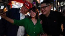 Seorang wanita berswafoto dengan peniru pemimpin Korea Utara Kim Jong-un dan peniru Presiden AS, Donald Trump selama gelaran KTT G20 di Osaka, Jepang, Jumat (28/6/2019). Sejumlah pemimpin dunia berkumpul dalam KTT G20 yang berlangsung dua hari di Osaka. (Charly TRIBALLEAU/AFP)