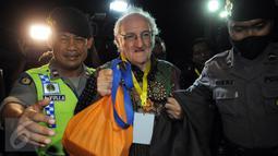 Rohaniawan pendamping narapidana Romo Carolus dikawal petugas saat menyeberang ke Pulau Nusa Kambangan, Cilacap, Jateng, (28/7). Rohaniawan dipanggil masuk ke Pulau Nusa Kambangan, jelang pelaksanaan eksekusi mati tahap III. (Liputan6.com/Helmi Afandi)