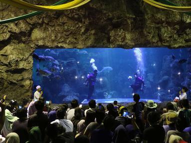 Pengunjung menyaksikan penyelam saat bermain bola di dalam aquarium Sea World, Jakarta, Sabtu (16/6). Atraksi tersebut digelar dalam rangka menyemarakkan ajang Piala Dunia 2018 yang berlangsung di Rusia. (Liputan6.com/Immanuel Antonius)