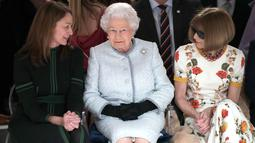 Ratu Elizabeth II berbincang dengan chief executive British Fashion Council, Caroline Rush dan Ratu Fashion, Anna Wintour (kanan) ketika menonton pagelaran London Fashion Week 2018, Selasa (20/2). (Yui Mok/Pool photo via AP)