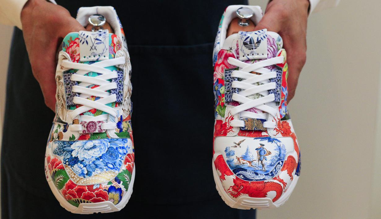 Pekerja memegang sepatu kets unik kolaborasi Adidas dan produsen porselen Meisse bernama Porcelain ZX8000, saat pratinjau di rumah lelang Sotheby di New York City pada 4 Desember 2020. Sepatu yang akan dilelang bulan ini diperkirakan terjual dengan nilai hingga 1 juta dollar AS. (Kena Betancur/AFP)