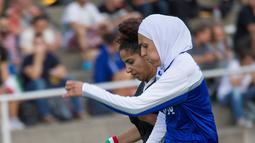 Pemain wanita Iran berebut bola dengan pemain wanita Jerman saat pertandingan Discover Football tournament di Berlin, Jerman (31/8). Pesepakbola wanita Iran tampak antusias dengan turnamen ini. (REUTERS/Stefanie Loos)