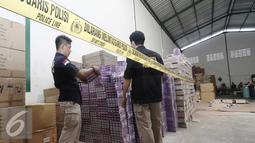 Petugas memeriksa Barang bukti obat palsu di pergudangan Surya Balaraja, Tangerang, Kamis (26/11). Obat berbahaya tersebut tidak memiliki ijin dan berbahaya bagi kesehatan kulit manusia. (Liputan6.com/Angga Yuniar)