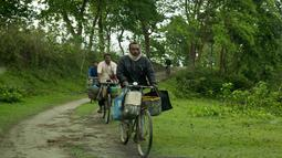 Nelayan mengendarai sepeda untuk membeli ikan di tepi sungai Brahmaputra, India (3/4). Assam sangat kaya akan sumber daya airnya. Brahmaputra adalah salah satu sungai terbesar di Asia, yang melewati wilayah China Tibet, India dan Bangladesh sebelum konvergen ke Teluk Benggala. (AP Photo/Anupam Nath)
