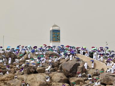 Jemaah haji berkumpul di sekitar Jabal al-Rahma (Gunung Rahmat) saat menunaikan prosesi wukuf di Padang Arafah, tenggara Kota Suci Mekah, Arab Saudi, Senin (19/7/2021). Wukuf di Padang Arafah menjadi puncak ibadah selama prosesi haji. (FAYEZ NURELDINE/AFP)