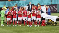 Para pemain Denmark membuat brikade untuk menutupi Christian Eriksen yang jatuh pingsan saat melawan Finlandia pada laga Piala Eropa di Stadion Parken (12/6/2021). (AFP/Wlofgang Ratttay)